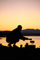 A woman cooks breakfast while camping along the shore of Jackson Lake in  Grand Teton National Park, Jackson Hole, Wyoming.