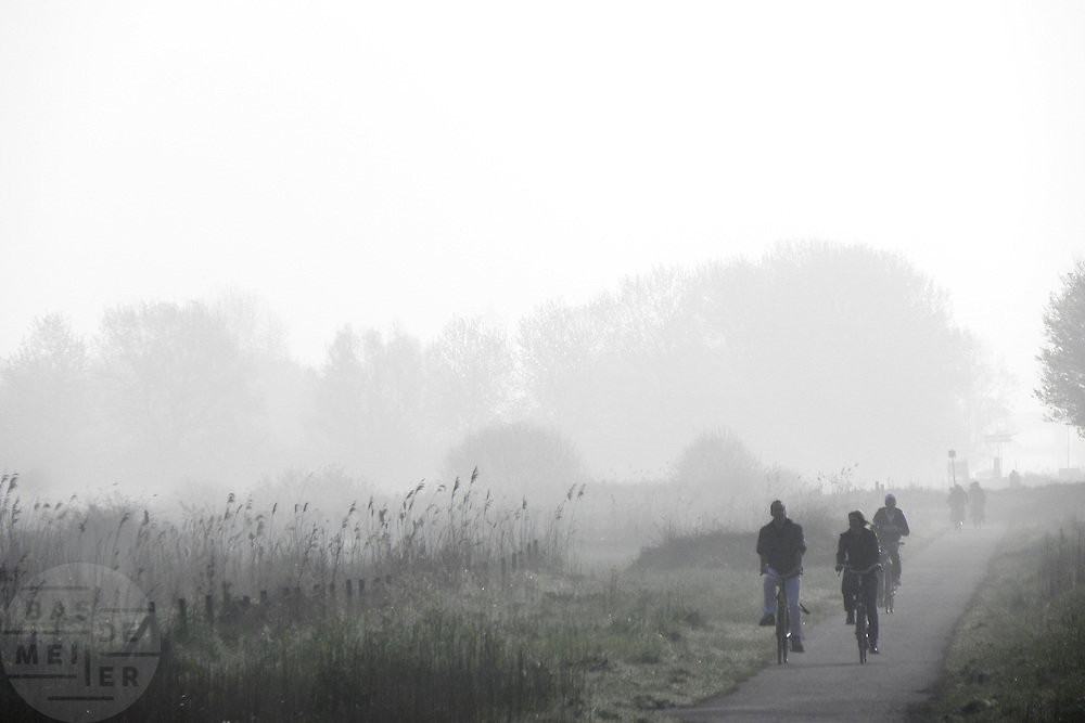 Een groep mensen fietst in de ochtend door de Waarderpolder.<br />