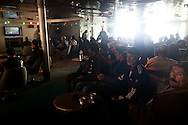 Tunisians watch AL Jazeera on board a vessel heading to  Tunis in Benghazi on Feb. 26, 2011, many people from poorer countries are stranded in Libya.