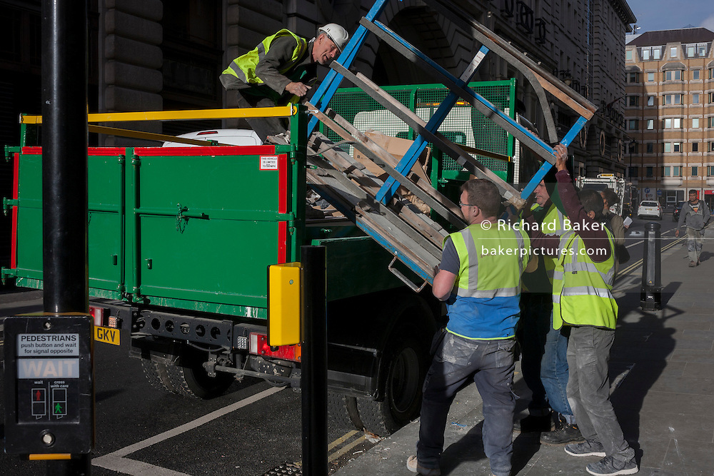 Workmen together load retail-related refuse into a lorry in central London.