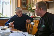 Farmer Howell Williams and Chris Blake of The Green Valleys  sitting in the farm kitchen discussing the 15kW micro hydro power generator producing electricity at Abercrave Farm on the Brecon Beacons, Wales.