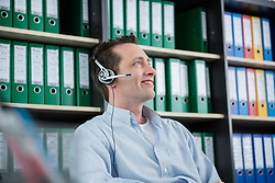 Young man portrait sitting office headset smiling