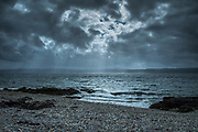 Rays of the sun breaking through dark clouds over the seashore on northern coast of the Isle of Arran, Scotland
