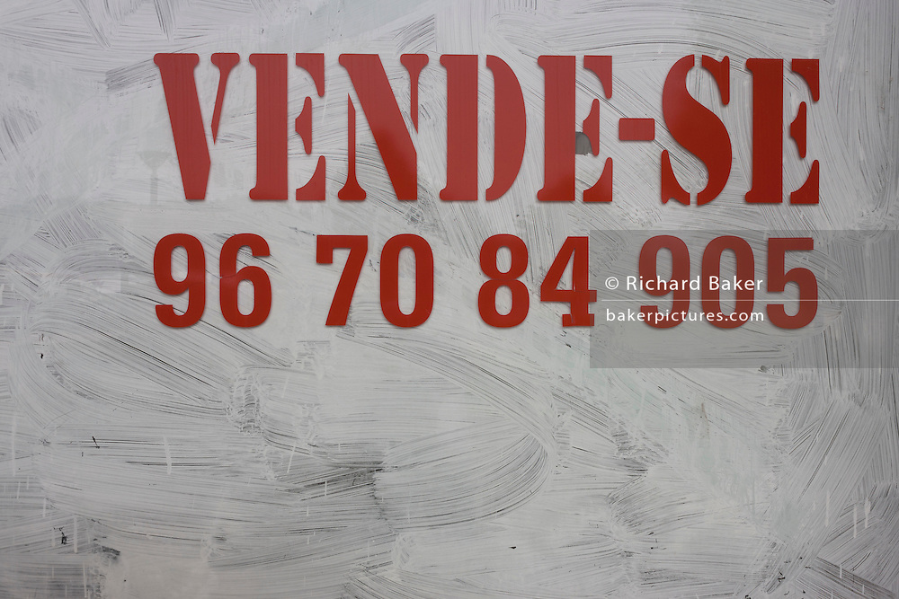 Detail of a whitewashed window of a closed business, soon to re-open in the market town of Estarreja, Portugal.