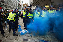 A Metropolitan Police officer picks up a smoke grenade set off by students attending a National Demonstration for a Free Education on 4th November 2015 in London, United Kingdom. The demonstration was organised by the National Campaign Against Fees and Cuts (NCAFC) in protest against tuition fees and the Government's plans to axe maintenance grants from 2016.