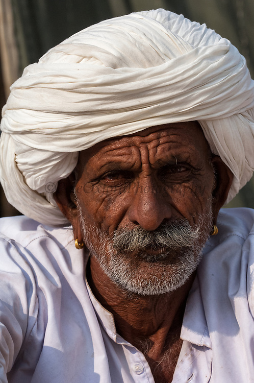 Rajusthani pastoralist at the Pushkar camel and livestock fair which takes place in the Hindu month of Kartik (October / November) ten days after Diwali (Festival of Lights). The pastoralists generally wear a white cotton dhoti (Strip of fabric tied into pants) and white jackets and turbans. The traditional pipe is called a 'Chilum'.<br /> Pushkar has always been the the region's main market for herdsman and farmers buying and selling camels, horses, indigenous breeds of cattle and even elephants. Over the years this annual trading event has increased in volume to become one of the largest in Asia. Temporary tents and campsites suddenly appear to accomodate the thousands of pilgrims, villagers and tourists. Entertainers and contests abound and a festive funfair atmosphere prevails over Pushkar during the Mela's 2 week duration. Thousands of men come first with their camels, horses and cattle and camp on the dunes to transact business. 3 days before the full moon the women arrive beautifully attired. The town of Pushkar is one of the holiest centers of Hinduism and houses one of the few Brahma Temples in India. It is one of the 5 essential pilgrimage centers which a Hindu must visit in his lifetime along with Badrinath, Puri, Rameshwaram and Dwarka. The 12 day fair culminates in a religious Hindu pilgrimage and reaches a crescendo on the night of the full moon (Purnima) when pilgrims take a dip in the holy lake.  <br /> Pushkar, Rajasthan. INDIA