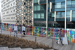 © Licensed to London News Pictures. 27/03/2021. London, UK. Local residents walk across the new art installation titled Hundreds and Thousands by artist Liz West for The Tide. The outdoor art work is installed on the new elevated riverside trail, The Tide, on the Greenwich Peninsula. 700m of the walkways glass balustrades are covered by a ribbon of colour. Hundreds and Thousands is presented by NOW Gallery.<br />  credit: Ray Tang/LNP