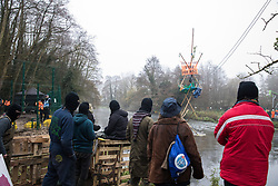 Denham, UK. 7th December, 2020. Anti-HS2 activists observe Dan Hooper, better known as roads protester Swampy during the 1990s, on a tripod positioned in the river Colne in order to try to delay bridge building works in connection with the HS2 high-speed rail link. Activists continue to resist the controversial £106bn rail project from a series of protest camps based along its initial route between London and Birmingham.