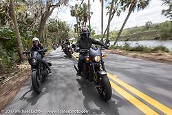 Iron Lilly Kristen Lassen (L) riding a Harley-Davidson Sportster alongside custom bike builder Jesse Rooke through Tomoka State Park during Daytona Beach Bike Week. FL. USA. Tuesday, March 14, 2017. Photography ©2017 Michael Lichter.
