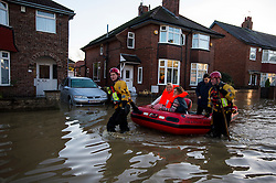 © Licensed to London News Pictures. 27/12/2015. York, UK.  Two women being rescued from her home by Mountain Rescue on Huntington Road in central York. Large areas of the North of England have been hit by severe flooding following unusually heavy rainfall in December. Photo credit: Ben Cawthra/LNP