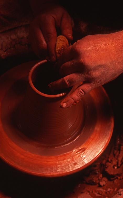 Potter works on potters wheel<br /> making redware, Berks Co., PA