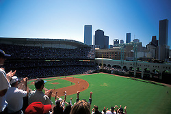 Crowd cheering at Minute Maid Park during an Astros baseball game with the Houston skyline in background.
