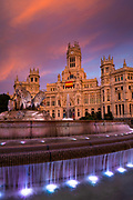 """The Plaza de Cibeles is a square with a neo-classical complex of marble sculptures with fountains that has become an iconic symbol for the city of Madrid. It sits at the intersection of Calle de Alcalá (running from east to west), Paseo de Recoletos (to the North) and Paseo del Prado (to the south). Plaza de Cibeles was originally named Plaza de Madrid, but in 1900, the City Council named it Plaza de Castelar, which was eventually replaced by its current name.<br /> <br /> It is currently delimited by four prominent buildings: the Bank of Spain Building, the Palacio de Buenavista, the Palace of Linares (""""Palacio de Linares""""), and the Cybele Palace (""""Palacio de Cibeles""""). These constructions are located in four different neighbourhoods from three different adjacent districts: Centro, Retiro, and Salamanca.<br /> <br /> Over the years, Cybele Palace and her fountain have become symbolic monuments of the city. The fountain of Cybele is found in the part of Madrid commonly called the Paseo de Recoletos. This fountain is named after Cybele, a Phrygian goddess. The fountain is traditionally the place where Real Madrid C.F. celebrate their team victories, with the team captain placing a Real Madrid flag and scarf on the statue.["""