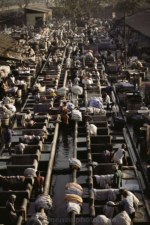 """Washing clothes at the Dhobi ghats, Bombay, India. The dhobi is a traditional laundryman, who collects your dirty linen, washes it, and returns it neatly pressed to your doorstep. The """"laundries"""" are called """"ghats"""": row upon row of concrete washtubs.."""