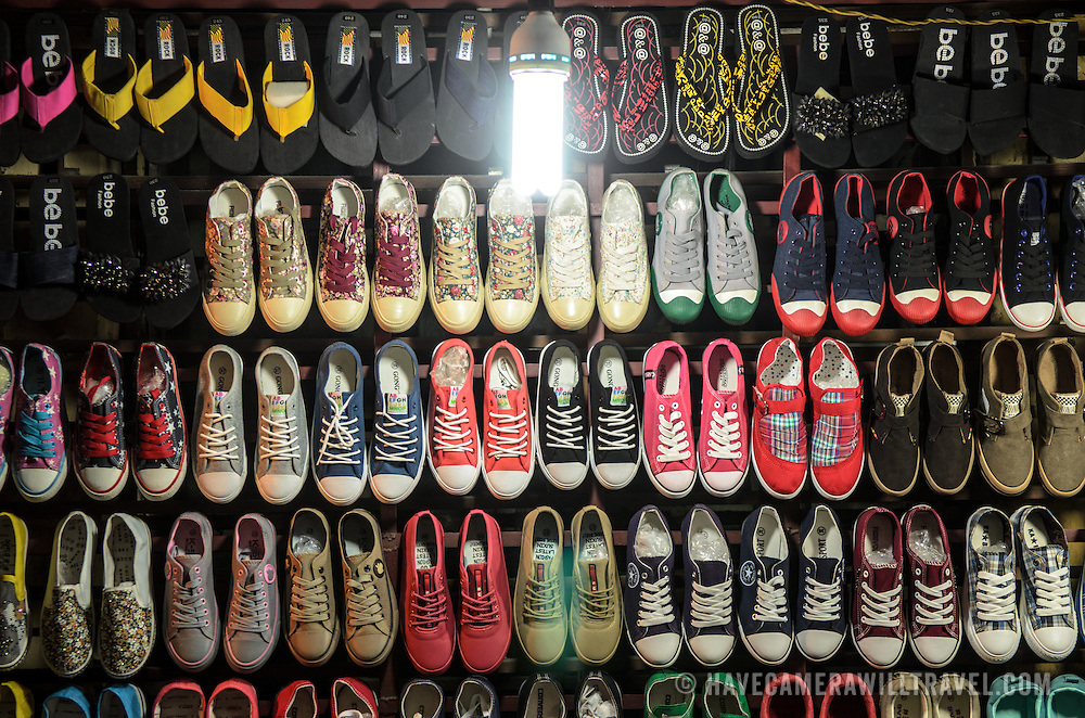 Rows of shoes for sale on a wall of a market stall in Hanoi's Old Quarter.