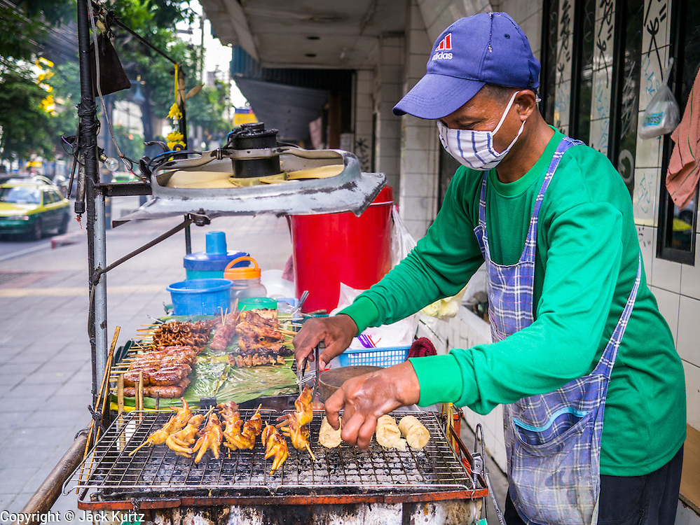 """04 OCTOBER 2012 - BANGKOK, THAILAND: A grilled meat vendor works at his stand on Sukhumvit Rd in Bangkok, Thailand. He sells grilled chicken's feet and Thai sausage. Thailand in general, and Bangkok in particular, has a vibrant tradition of street food and """"eating on the run."""" In recent years, Bangkok's street food has become something of an international landmark and is being written about in glossy travel magazines and in the pages of the New York Times.       PHOTO BY JACK KURTZ"""