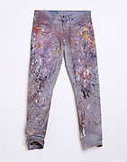 Jeans with a lot of paint splatters front view.
