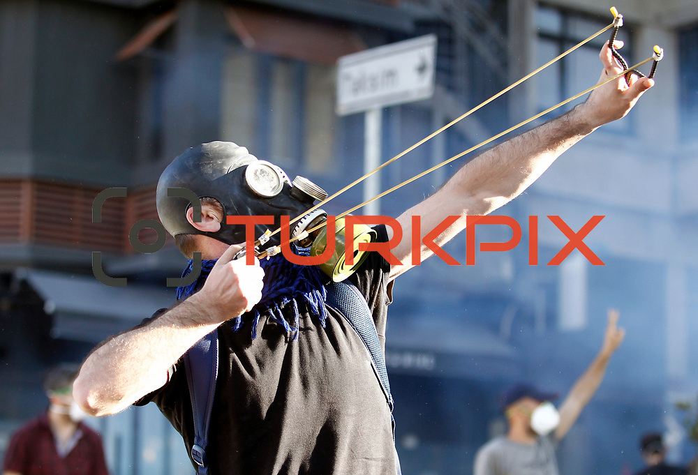 A protester uses a slingshot to throw stones at riot police during a protest at Taksim Square in Istanbul June 11, 2013. Turkish riot police fired tear gas and water cannon at hundreds of protesters armed with rocks and fireworks on Tuesday as they tried to take back control of a central Istanbul square at the heart of fierce anti-government demonstrations.