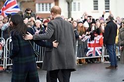 Meghan Markle and Prince Harry reach out for one another while on a walkabout on the esplanade at Edinburgh Castle, as she and Prince Harry visited Scotland.