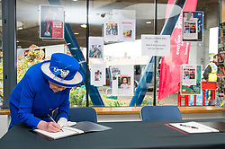 Queen Elizabeth II signs a book on condolence during a visit to the Westway Sports Centre, London, which is providing temporary shelter for those who have been made homeless in the Grenfell Tower disaster.