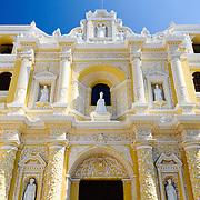 Front of the building of the distinctive  and ornate yellow and white exterior of the Iglesia y Convento de Nuestra Senora de la Merced in downtown Antigua, Guatemala.