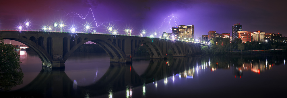 Lightning flashes across the sky over the Francis Scott Key Bridge. As seen from the overlook of the former Aqueduct Bridge. Washington, D.C.