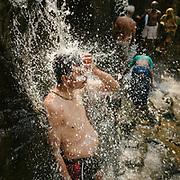 A man washed under a waterfall in Madya Pradesh.