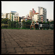 Friends are talking, sitting on a bench in a small park along Truc Bach Lake in Hanoi, Vietnam, Asia