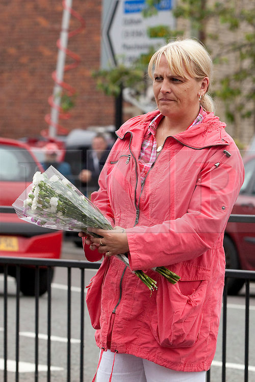 © Licensed to London News Pictures. 26/06/2012. Oldham , UK . A large explosion , believed to be caused by gas , has brought down at least one house in an Oldham terrace. A woman lays flowers alongside other tributes at the scene . Photo credit : Joel Goodman/LNP