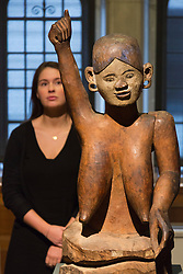 "© Licensed to London News Pictures. 30/01/2014. London, England. Picture: A museum worker poses with the wooden sculpture ""Maria"", about 1903/4, collected on Nankauri Island, in the Nicobar Islands, Bay of Bengal from the Museum of Archaeology and Anthropology.<br />  The Exhibition ""Discoveries - Art, Science & Exploration"" from the University of Cambridge Museums opens at Two Temple Place, Embankment, London on 31 January and runs until 27 April 2014. Photo credit: Bettina Strenske/LNP"