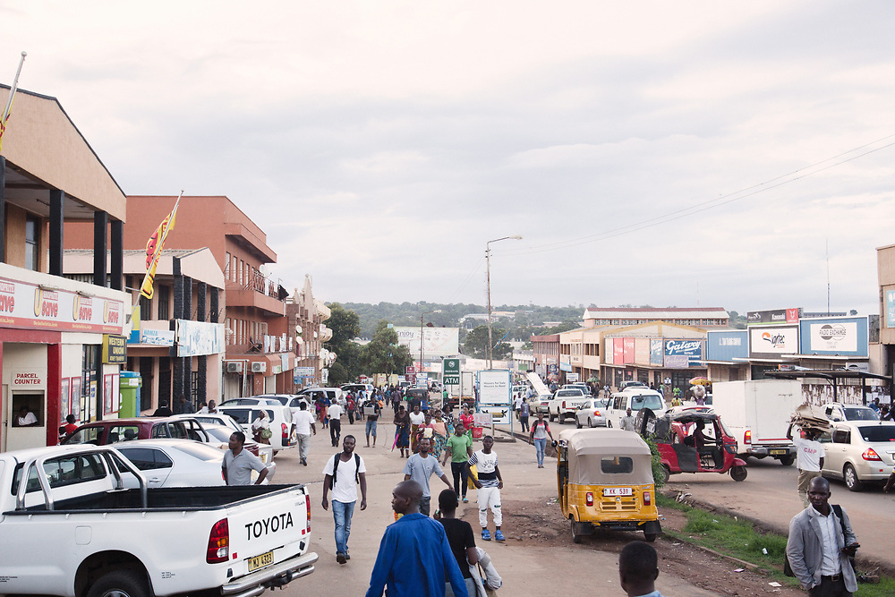 INDIVIDUAL(S) PHOTOGRAPHED: N/A. LOCATION: Lilongwe, Malawi. CAPTION: People and cars weave in and out of the street and parking spaces in Lilongwe, Malawi.