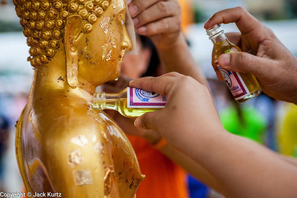 13 APRIL 2013 - BANGKOK, THAILAND: People anoint a statue of the Buddha with scented oils in front of the Bangkok City Hall building on Songkran. Songkran is the traditional Thai New Year's Festival. It is held April 13-16. Many Thais mark the holiday by going to temples and making merit by giving extra alms to monks or offering extra prayers. They also mark Songkran with joyous water fights. Songkran has been a national holiday since 1940, when Thailand moved the first day of the year to January 1.    PHOTO BY JACK KURTZ