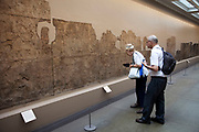 The British Museum, London. Visitors look closely at an ancient stone freize from Southern Iraq.