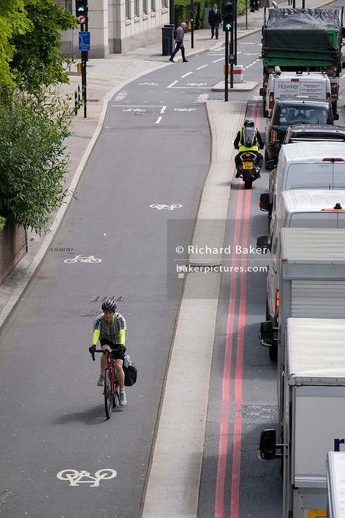 A cyclist rides westwards against the direction of queued traffic on Upper Thames Street in the City of London, the capital's financial district, on 22nd June 2021, in London, England.