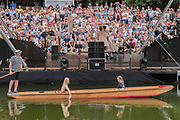 Peopel on the lakeside and on punts enjoy Country from Town and Country by Matthew Bourne performed by New Adventures for Sadlers Wells on the Waterfront Stage - The 2017 Latitude Festival, Henham Park. Suffolk 15 July 2017