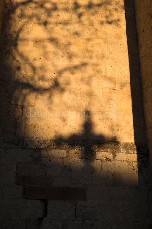 Shadow of a cross - the Creu de Terme on the wall of the Monastery of Sant Cugat, Barcelona, Catalonia, Spain. Monestir de Sant Cugat, Catalunya, Espanya. The cross was originally a boundary marker for the town, and lads of the monastery.