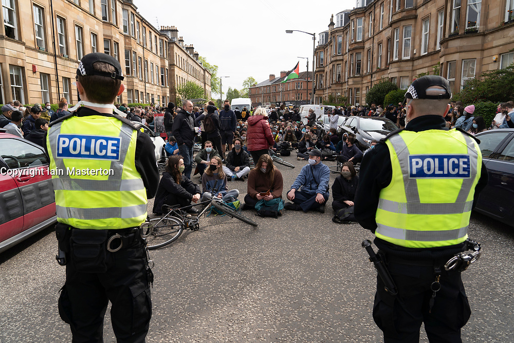 Glasgow, Scotland, UK. 13 May 2021. Protesters gather in Pollokshields to prevent the deportation of individual from household. Heavy police presence continues with a tense stand-off between the police and protesters who are sitting in Kenmure Street Street blocking access. Iain Masterton/Alamy Live News