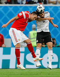 June 19, 2018 - Saint Petersburg, Russia - Artem Dzyuba (L) of Russia national team and Ahmed Hegazy of Egypt national team vie for a header during the 2018 FIFA World Cup Russia group A match between Russia and Egypt on June 19, 2018 at Saint Petersburg Stadium in Saint Petersburg, Russia. (Credit Image: © Mike Kireev/NurPhoto via ZUMA Press)