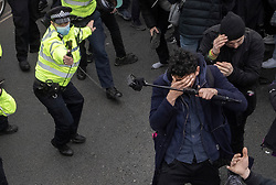 © Licensed to London News Pictures. 03/04/2021. London, UK. A police officer uses pepper spray as scuffles break out in Parliament Square during a Kill the Bill demonstration in central London. A coalition of groups including Extinction Rebellion, Kill the Bill & Black Lives Matter are coming together over the Easter weekend to campaign against the proposed Police, Crime, Sentencing and Courts Bill which will give police in England and Wales more power to impose conditions on non-violent protests. Photo credit: Peter Macdiarmid/LNP