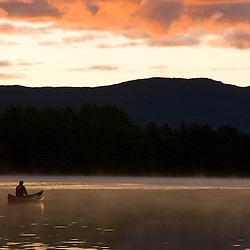 Canoeing at sunrise on Prong Pond near Moosehead Lake Maine USA