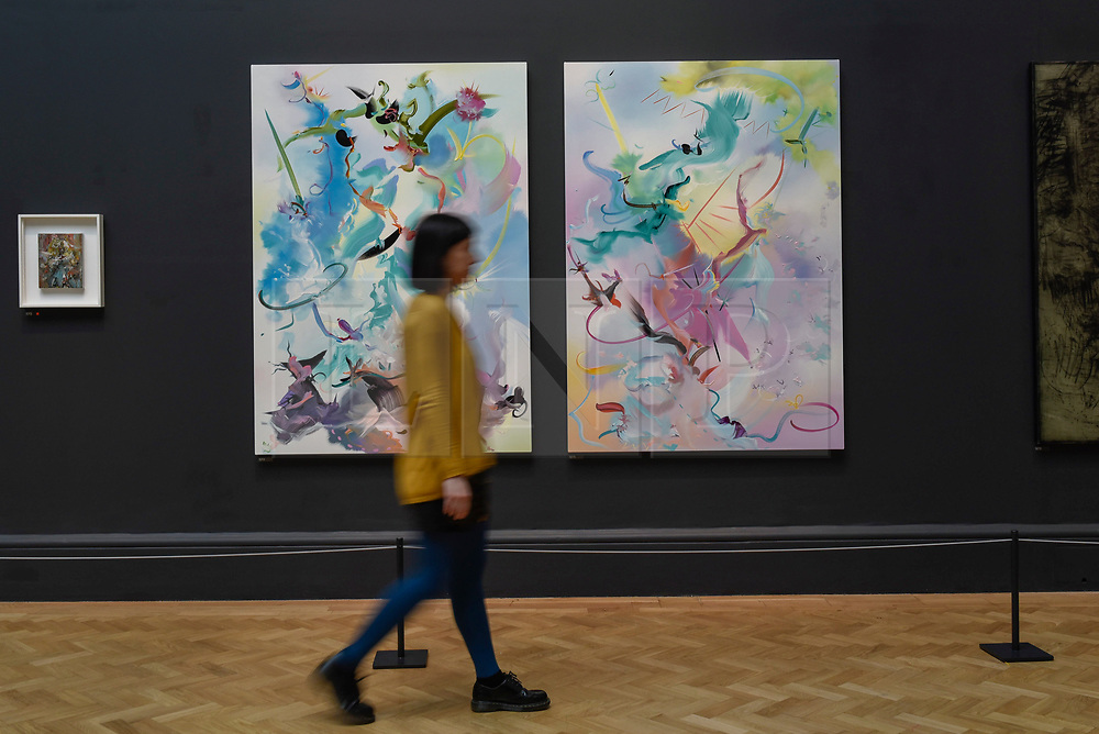 """© Licensed to London News Pictures. 08/06/2017. London, UK. A visitor walks in front of (L to R) """"She Pricked Her Fingers Cutting The Clouds"""" and """"Many-Coloured Messenger Seeks Her Fortune"""" both by Fiona Rae RA. Preview of the Summer Exhibition 2017 at the Royal Academy of Arts in Piccadilly.  Co-ordinated by Royal Academician Eileen Cooper, the 249th Summer Exhibition is the world's largest open submission exhibition with around 1,100 works on display by high profile and up and coming artists.<br />  Photo credit : Stephen Chung/LNP"""
