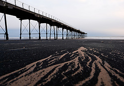 © Licensed to London News Pictures.09/02/16<br /> Saltburn-by-the-Sea, UK. <br /> <br /> Sea coal lies on the sand on the beach at Saltburn by the Sea in North Yorkshire. Sea coal is coal that has been washed up on the beach, coming from coal seams in sea cliffs or underwater deposits. Used for centuries this coal was collected and used for cooking, heating and forging metals. <br /> Photo credit : Ian Forsyth/LNP