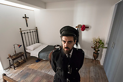 "© Licensed to London News Pictures. 13/11/2018. LONDON, UK. A staff member, posing as a prison guard, in Ruth Ellis' prison cell.  Preview of ""Glad I Did It"", a new work by Irish artist Christina Reihill at Bermondsey Project Space.  The interactive artwork looks at the life and death of Ruth Ellis, the last woman to be hanged in Britain, after she shot her lover, racing driver, David Blakely in 1955.  On display are the artist's interpretation of Ruth Ellis' prison cell, including furniture and props, the hanging room together with a video display of the artist in conversation.   The show runs 14 November to 1 December 2018.  Photo credit: Stephen Chung/LNP"