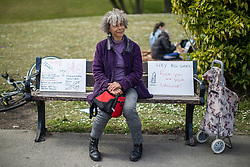 """© Licensed to London News Pictures. 16/05/2020. Manchester, UK. A women sits on a bench alongside placards reading """" No mandatory vaccines """" , """" Beware Poison """" """" No 5G """" and """" Hey Bill Gates Fuck you and your vaccine """" . An anti-lockdown, """"mass gathering"""" demonstration is held in Platt Fields Park in protest at government measures to control the spread of Covid-19. A group calling itself the UK Freedom Movement has organised a series of demonstrations across the UK. Photo credit: Joel Goodman/LNP"""