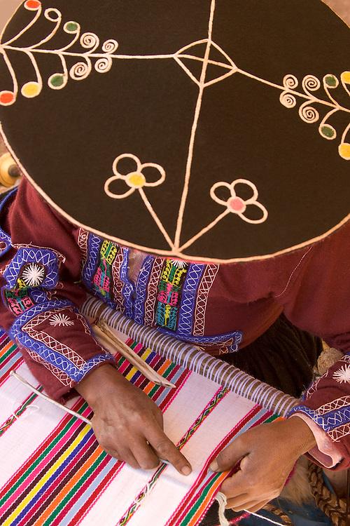 South America, Peru, Raqchi (near Cuzco), woman in traditional hat weaving using backstrap loom.