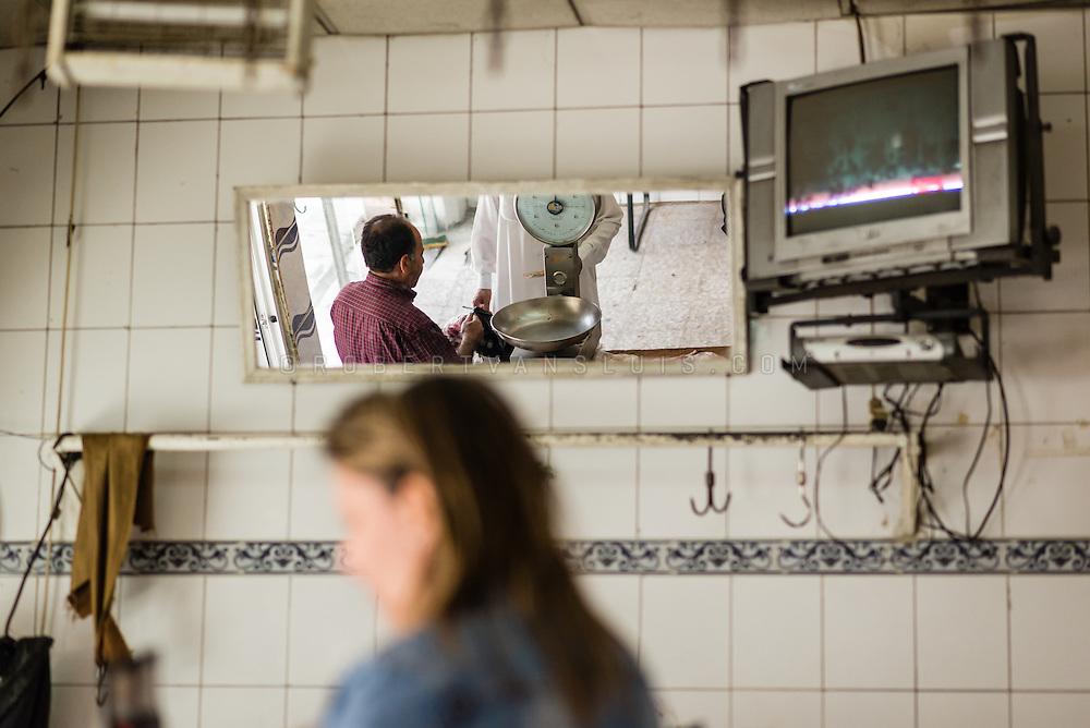 A butcher sells meat in a butcher's shop in Madaba, Jordan. Photo © Robert van Sluis