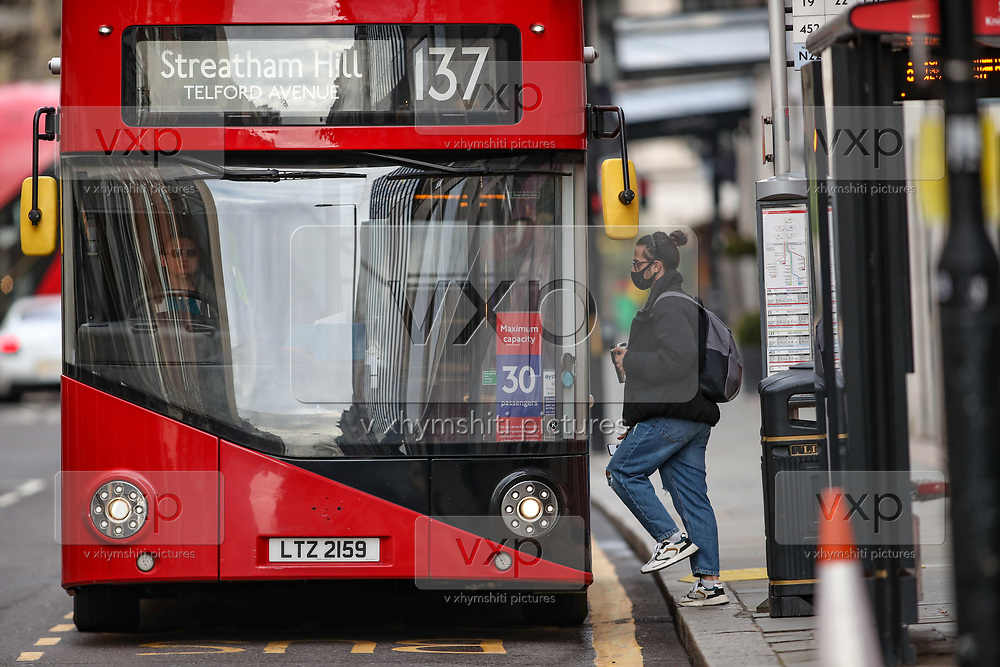 A member of public wearing face surgical protective mask walks in a red bus nearby Knights Bridge station in central London on Sunday, Mar 14, 2021. Coronavirus has hit the UK hard, with the country recording more than 3m cases and 125,000 deaths linked to the disease. (VXP Photo/ Vudi Xhymshiti)