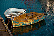 SUBJECT: Skiffs tethered to dock. IMAGE: Anything but pampered, these characters grace the inner harbor at Rockport, Massachusetts, with the colors of surrounding boats and buildings reflecting in the ruffled water.