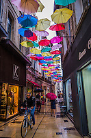 The artist Patricia Cunha produced a work Umbrella Sky along Rue des Fourbisseurs in Avignon. Pedestrians can view some 160 umbrellas suspended above their heads as a part of the Umbrella Sky Project which began in Agueda, Portugal.  Each summer during July, August and September artists construct these shady spots for pedestrians.  The array of umbrellas creates a geometric and colorful pattern overhead and helps keep the heat down. in an environmentally friendly way.