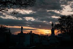 """Der Metairie Cemetery ist ein ländlicher Friedhof in New Orleans, Louisiana, USA. Der Name laesst faelschlicherweise vermuten, dass sich der Friedhof in Metairie, Louisiana, befindet. Er befindet sich jedoch innerhalb der Stadtgrenzen von New Orleans an der Metairie Road. Diese Grabstaette war zuvor eine Pferderennbahn, des 1838 gegründeten Metairie Race Course. Auf der Rennstrecke fand am 1. April 1854 das berühmte Lexington-Lecomte-Rennen statt, das als """"Norden gegen den Süden"""" -Rennen bezeichnet wurde. Der frühere Praesident Millard Fillmore war anwesend. Wegen des amerikanischen Bürgerkriegs wurde das Rennen eingestellt und als konfoederiertes Lager (Camp Moore) genutzt, bis David Farragut im April 1862 New Orleans für die Union einnahm. Der Metairie Cemetery wurde danach auf dem Gelände des alten Metairie Race Course errichtet. Im Bild ein Sonnenuntergang und Graeber, aufgenommen am 15.02.2020, New Orleans, Vereinigte Staaten von Amerika // Metairie Cemetery is a rural cemetery in New Orleans, Louisiana, United States. The name has caused some people to mistakenly presume that the cemetery is located in Metairie, Louisiana; but it is located within the New Orleans city limits, on Metairie Road (and formerly on the banks of the since filled-in Bayou Metairie). This site was previously a horse racing track, Metairie Race Course, founded in 1838. The race track was the site of the famous Lexington-Lecomte Race, April 1, 1854, billed as the """"North against the South"""" race. Former President Millard Fillmore attended. While racing was suspended because of the American Civil War, it was used as a Confederate Camp (Camp Moore) until David Farragut took New Orleans for the Union in April 1862. Metairie Cemetery was built upon the grounds of the old Metairie Race Course after it went bankrupt. The race track, which was owned by the Metairie Jockey Club, refused membership to Charles T. Howard, a local resident who had gained his wealth by starting the first Louisi"""